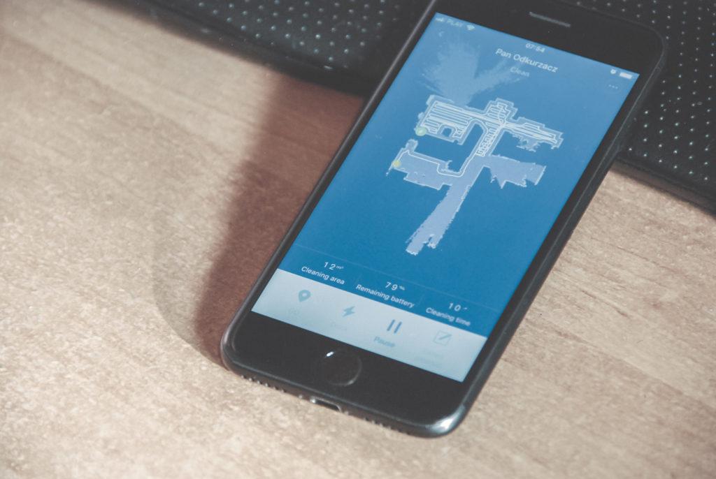 Na zdjęciu widać telefon z uruchomianą aplikacją Mi Home, leżący na biurku. W aplikacji widać akurat narysowaną przez robota mapę częściowo odkurzonego mieszkania, na której robot białą kreską zaznacza przejechaną trasę.
