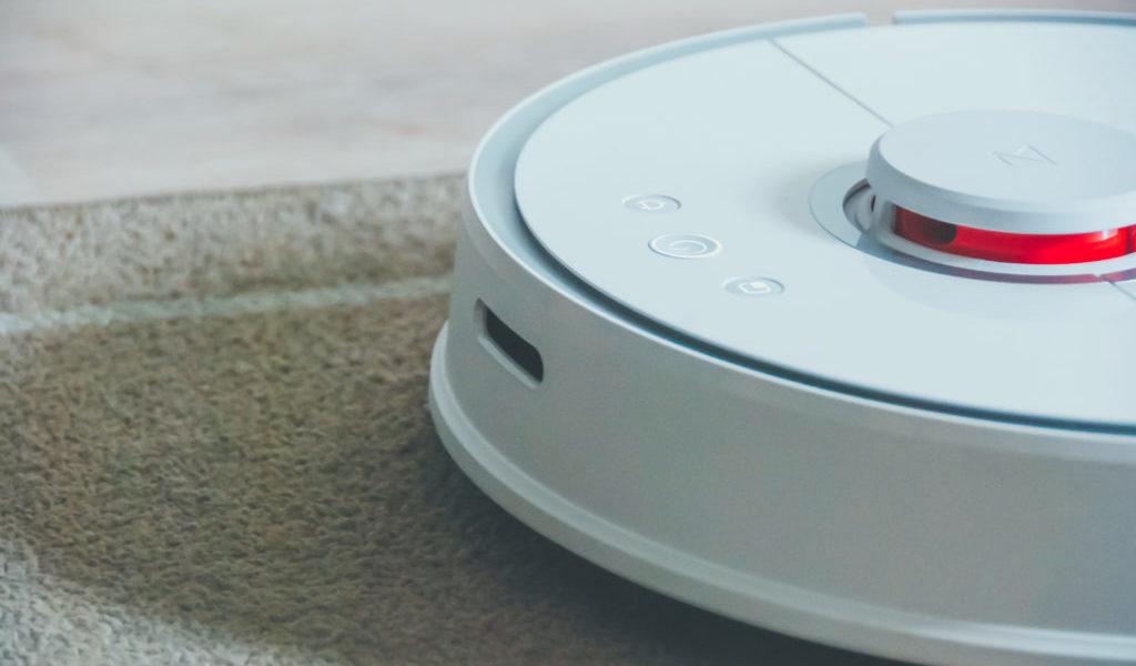 Zdjęcie ukazuje robota Roborocka S50 w zbliżeniu od przodu jadącego po dywanie. Wyraźnie widać trzy przyciski zarządzania urządzeniem obecne na górnej części urządzenia oraz wystający czujnik mierzący odległość elementów otoczenia.