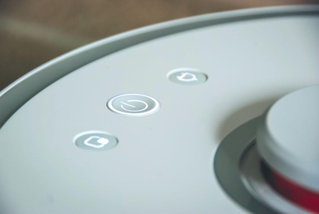 Zbliżenie na trzy główne przyciski zarządzające robotem obecne u góry Roborocka. Główny włącza i wyłącza urządzenie oraz zleca mu odkurzenie mieszkania. Jeden z dodatkowych nakazuje powrót do stacji dokującej, a drugi pozawala na uruchomienie sprzątania obszarowego.