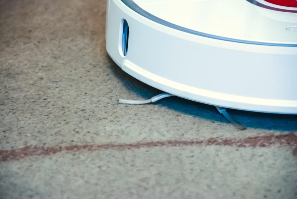 Zdjęcie przedstawia zbliżenie na robota Xiaomi Roborock S50 jadącego po dywanie i dodatkową boczną szczotkę wygarniającą. Szczotka ma trzy obracające się ramiona zakończone miękkim włosiem.