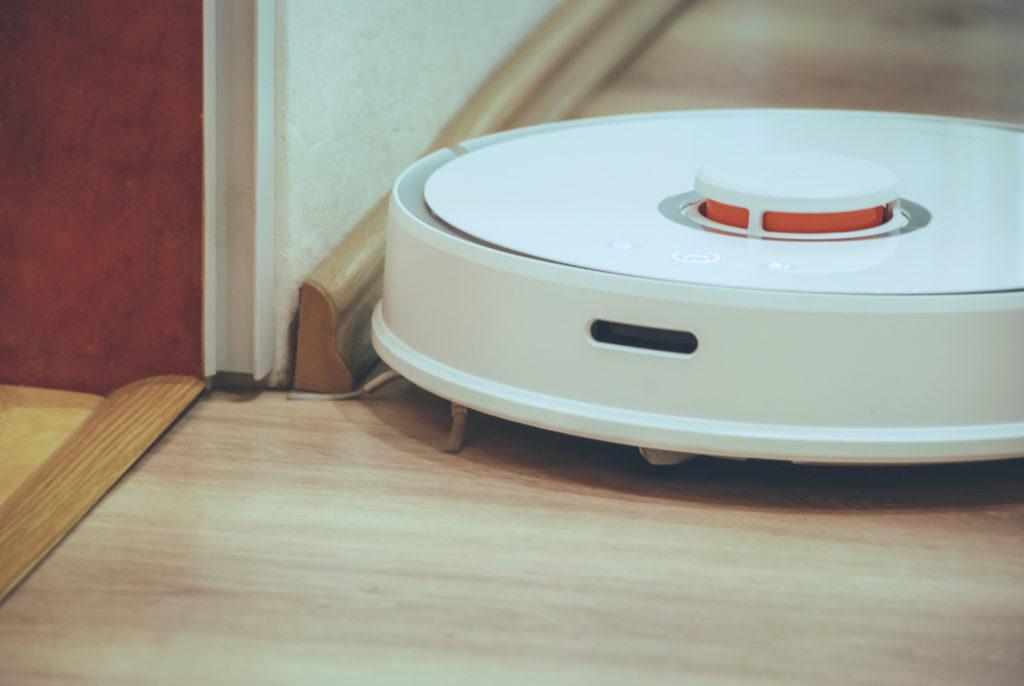 Na zdjęciu widać inteligentny odkurzacz Roborock S50 jadący tuż przy ścianie, który korzysta z dodatkowej kątowej szczotki do wyczyszczenia krawędzi i kątów mieszkania.