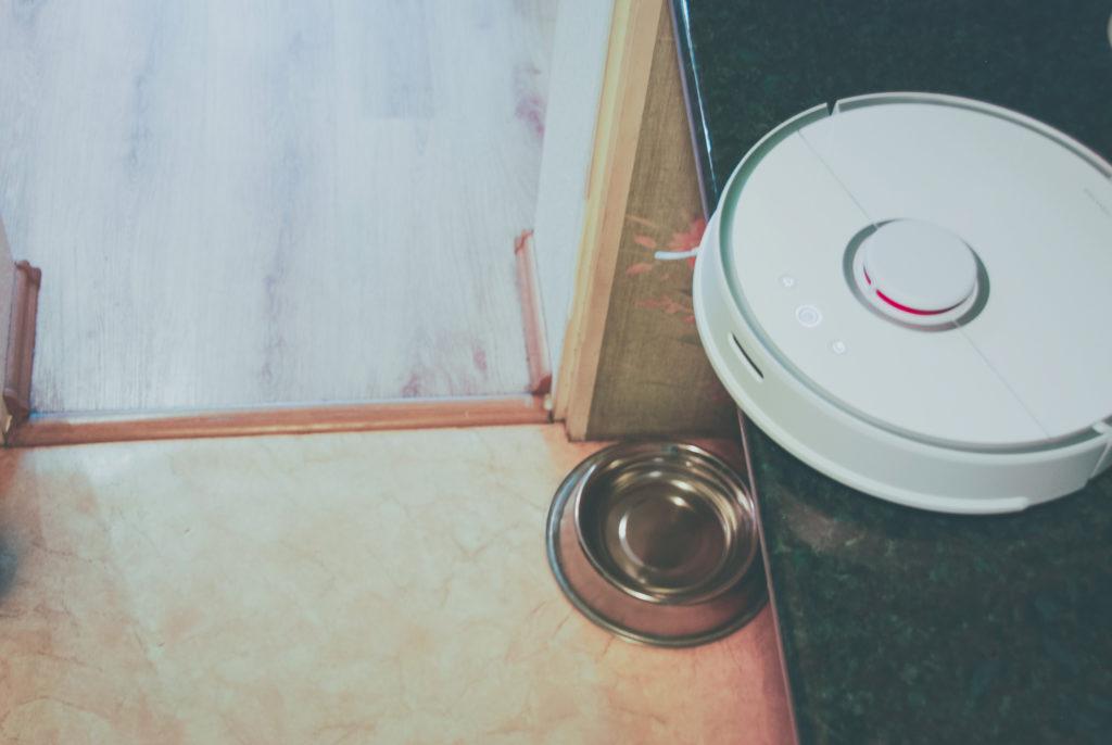 Zdjęcie pokazuje Roborocka na wysokim kuchennym blacie. Robot wystaje zaledwie 3 centrymetry poza jego krawędź, gdzie zatrzymał się sam dzięki czujnikom obecnym w podwoziu. W drugim planie widać podłogę około metra niżej.