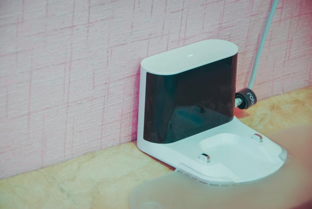 Na zdjęciu widać białą stację dokującą stojącą przy ścianie. Do stacji podłączona jest mata zabezpieczająca przed wilgocią od mopa, którego można używać z Roborockiem.