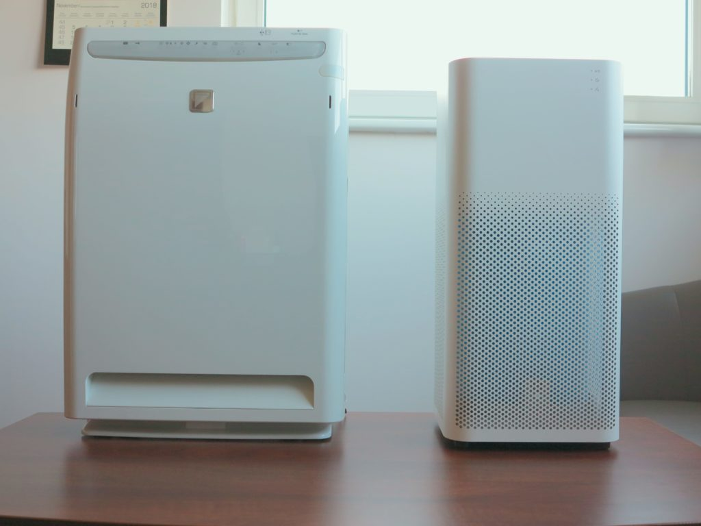 Na zdjęciu widać ustawione przodem do oglądającego, stojące obok siebie na biurku oczyszczacze powietrza Xiaomi model Air Purifier 2 oraz model MC70L od Daikin.