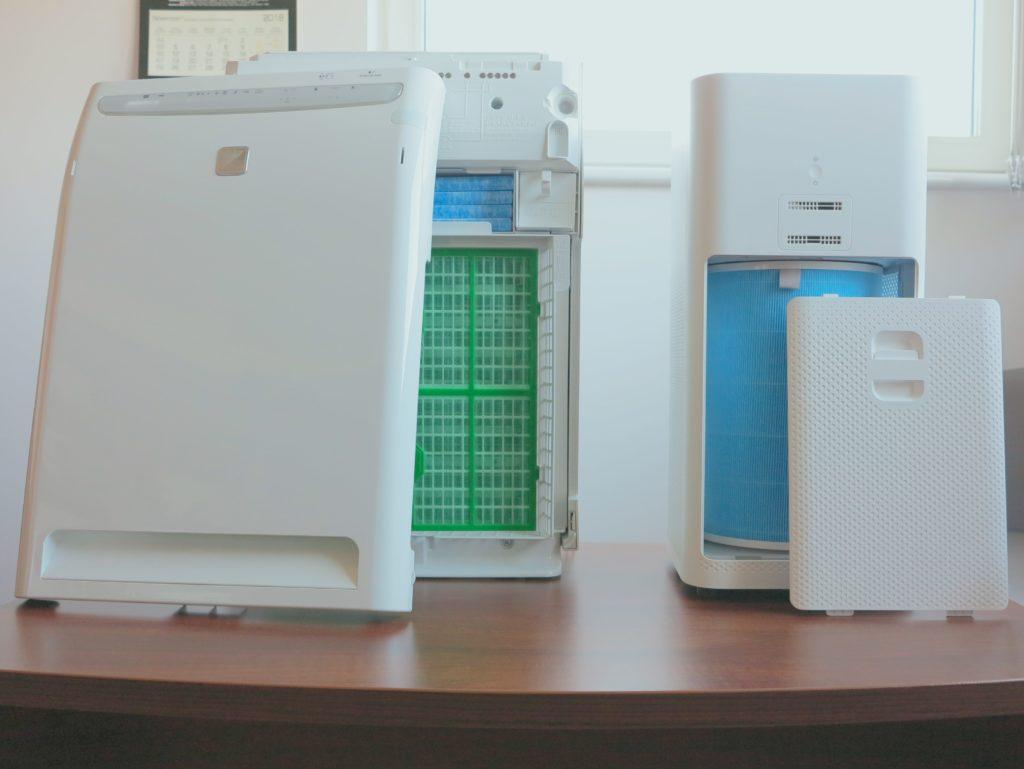 Zdjęcie pokazuje dwa oczyszczacze Daikin MC70L i Xiaomi Air Purifier 2 ustawione obok siebie na stole. Oba urządzenia mają zdjęte przednie panele, które postawione są przed nimi, a w środku oczyszczaczy widać ich filtry. Warstwowe w Daikinie oraz cylindryczny filtr 360 stopni w urządzeniu od Xiaomi.