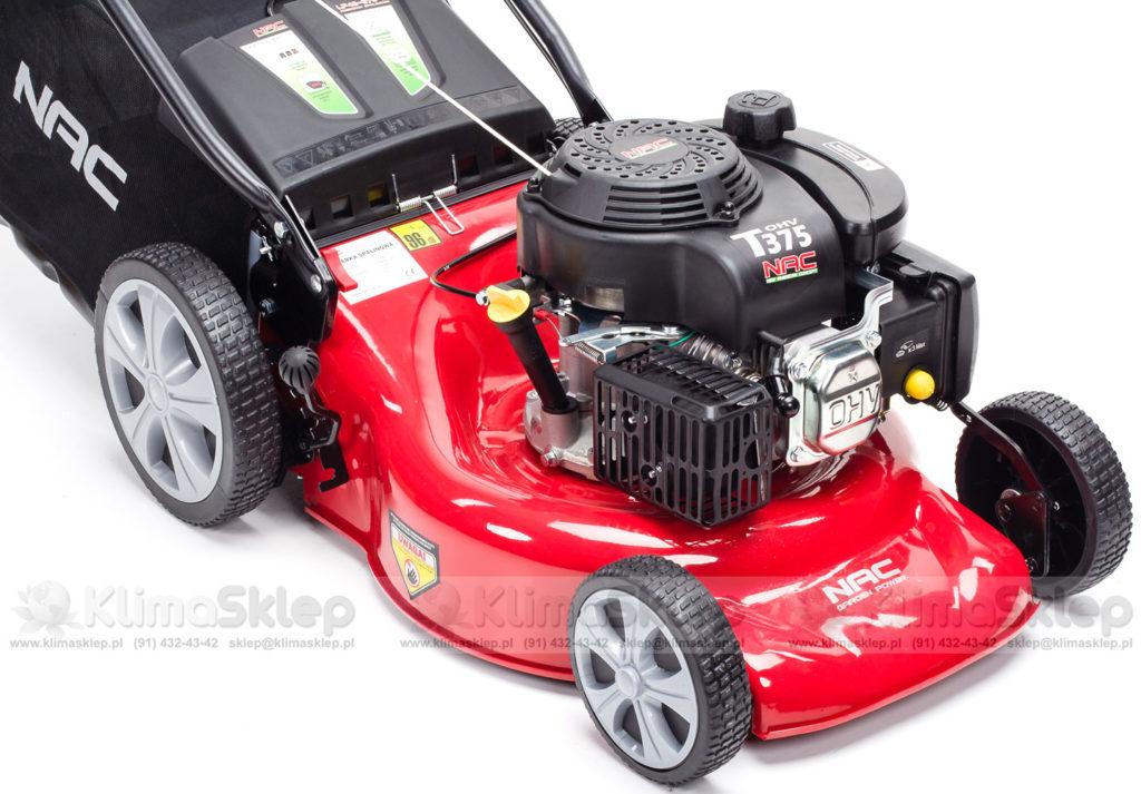 Zdjęcie przedstawia kosiarkę spalinową nac. Kosiarka jest koloru czerwonego, wyposażona jest w wytrzymały silnik.