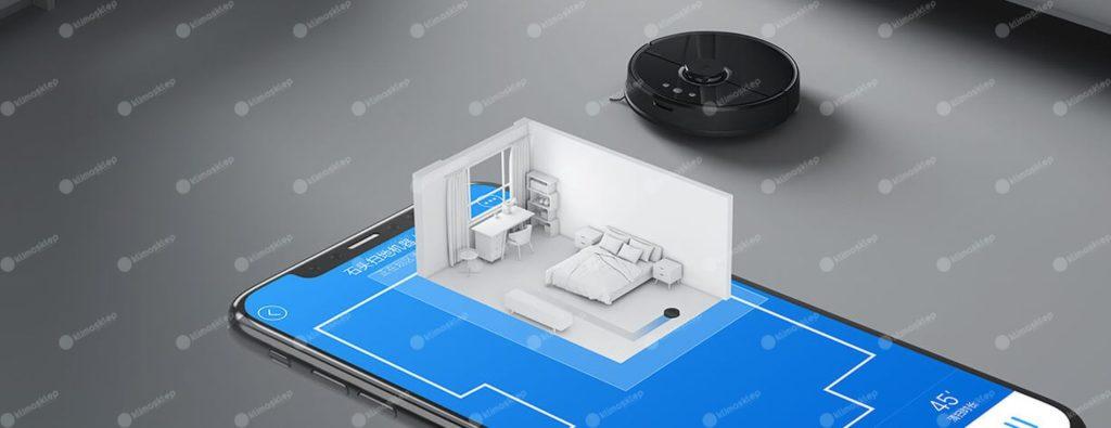 na zdjęciu przedstawiony jest robot xiaomi roborock w niecodziennym wydaniu. Robot w oddali zbliża się do postawionego na ziemi znacząco powiększonego smartfon-a, który ma włączoną aplikację. nieco nad telefonem unosi się coś podobnego do hologramu jednego z pomieszczeń będącym częścią mapy widniejącej na aplikacji. Robot prezentuje się znakomicie