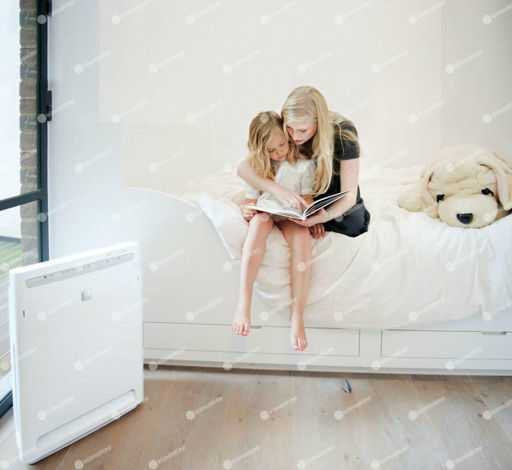 Daikin MC 70 w domu, oczyszczacz jest postawiony na podłodze, tuż przy mamie czytającej dla dziecka książkę. Oczyszczacz nie przeszkadza dzięki swojej niskiej głośności